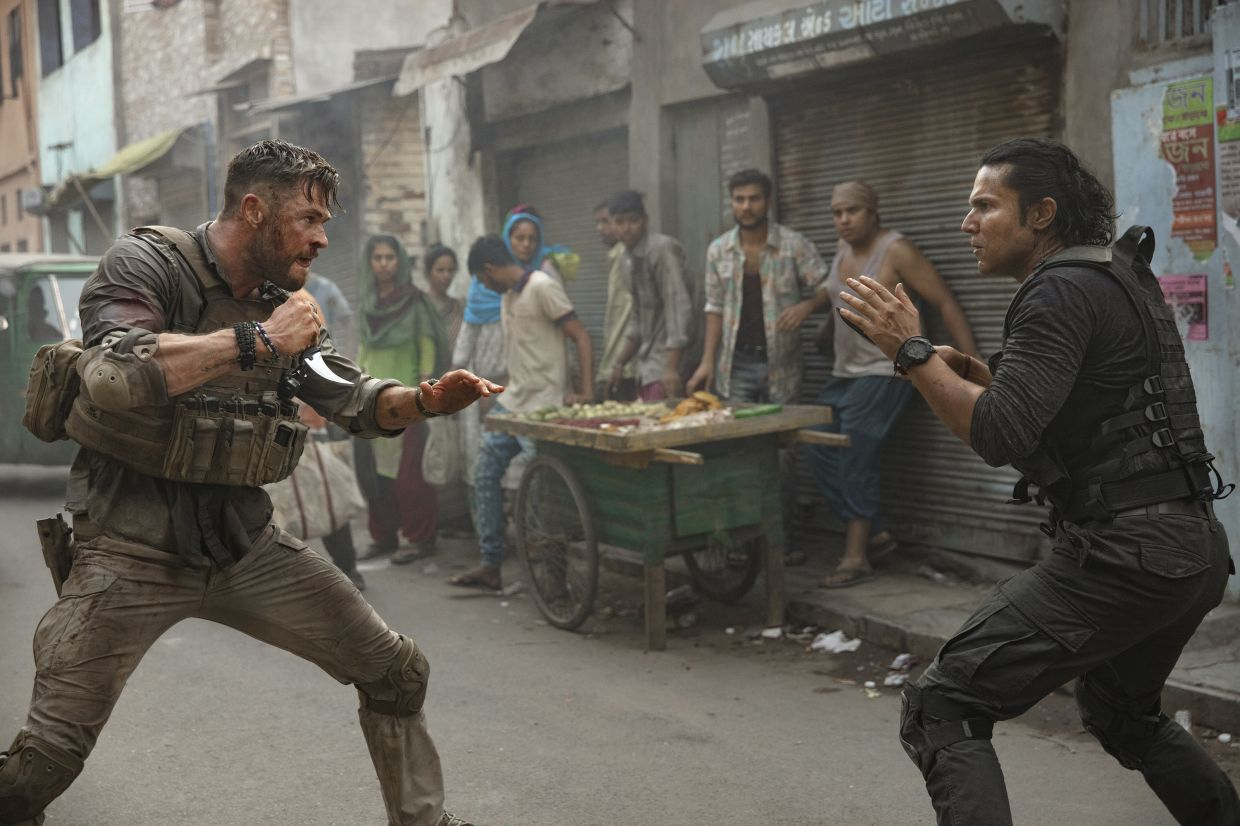 """This image released by Netflix shows Chris Hemsworth, left, in a scene from """"Extraction,"""" premiering this week on Netflix. (Jasin Boland/Netflix via AP)"""