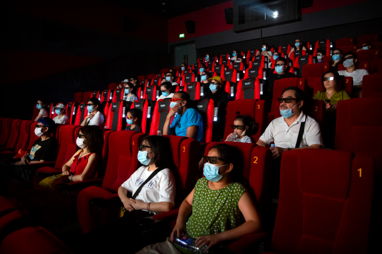 """People wearing face masks to protect against the coronavirus watch the film """"Dolittle"""" at a movie theater in Beijing, Friday, July 24, 2020. Beijing partially reopened movie theaters Friday as the threat from the coronavirus continues to recede in China's capital. (AP Photo/Mark Schiefelbein)"""
