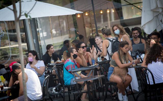 Israelis sit at a cafe in Tel Aviv, September 16, 2020. Photo by Miriam Alster/FLASH90 *** Local Caption *** קורונה תל אביב מסכה מסיכה מסכות בית קפה