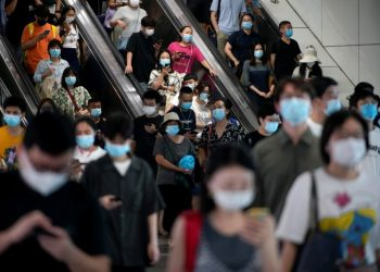 People wearing protective masks ride escalators inside a subway station, following new cases of the coronavirus disease (COVID-19), in Shanghai, China August 5, 2021. REUTERS/Aly Song